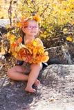 秋天拿着黄色叶子的画象婴孩 免版税库存照片