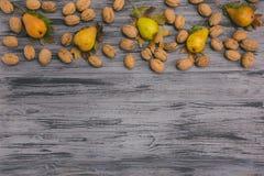 秋天收获梨和核桃在木桌上与文本 图库摄影