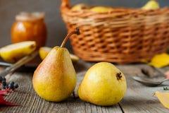 秋天收获概念-新鲜的成熟有机黄色梨用水在土气木桌,黑暗的石背景上滴下 Vegetaria 免版税图库摄影
