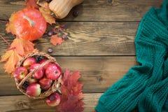 秋天收获,南瓜,在篮子的苹果,在木板的五颜六色的秋叶 仍然秋天生活 顶视图 免版税图库摄影