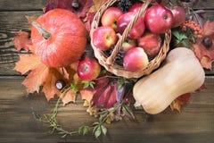 秋天收获,南瓜,在篮子的苹果,在木板的秋叶 秋天静物画,葡萄酒样式 顶视图 库存照片