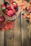 秋天收获,在篮子的苹果,在木板的五颜六色的秋叶 仍然秋天生活 顶视图 库存图片
