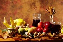 秋天收获:果子、叶子和酒 免版税库存照片
