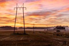 秋天日出、领域和输电线 库存照片