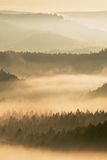 秋天日出 波希米亚的美丽的山 从黄色和橙色雾增加的小山树梢和峰顶镶边了由于str 免版税图库摄影