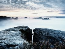 秋天早晨,在被暴露的岩石的看法对深谷充分轻的在破晓内的薄雾梦想的有薄雾的风景 库存图片