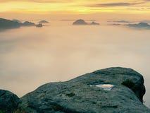 秋天早晨,在被暴露的岩石的看法对深谷充分轻的在破晓内的薄雾梦想的有薄雾的风景 免版税库存图片