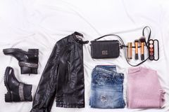 秋天时尚博客作者` s成套装备 桃红色羊毛编织了羊毛衫、蓝色牛仔裤从牛仔布,黑袋子和化妆brushs 免版税库存照片
