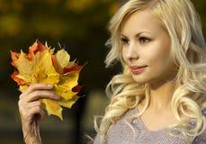 秋天时尚女孩。有黄色槭树的白肤金发的美丽的少妇在手中离开。外面。 免版税库存图片