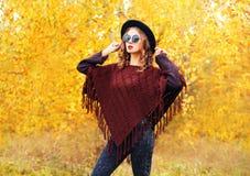 秋天时尚少妇模型佩带的黑帽会议太阳镜和被编织的雨披在黄色叶子 库存照片