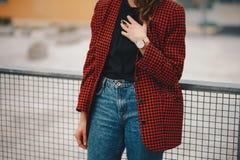 秋天时尚成套装备 在手边详述一个年轻时髦的女人的射击一件过大的短夹克的有金黄手表的 库存照片