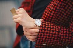 秋天时尚成套装备 在手边详述一个年轻时髦的女人的射击一件过大的短夹克的有金黄手表的 免版税库存图片