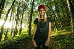 秋天时尚衣裳的美丽的白肤金发的妇女,在晴朗的秋天森林里 免版税库存图片