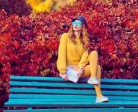 秋天时尚 长凳坐的妇女年轻人 库存图片