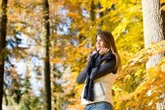 秋天时装模特儿公园放松妇女 免版税库存图片