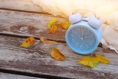 秋天时间变动的图象 后退概念 烘干叶子和葡萄酒闹钟在木桌上户外在下午 库存照片