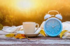 秋天时间变动的图象 后退概念 烘干叶子和葡萄酒闹钟在木桌上户外在下午 免版税库存照片
