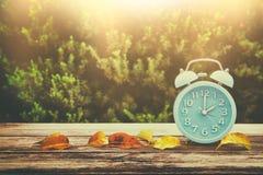 秋天时间变动的图象 后退概念 烘干叶子和葡萄酒闹钟在木桌上 库存图片