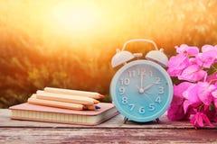 秋天时间变动的图象 后退概念 烘干叶子和葡萄酒闹钟在木桌上 免版税库存图片