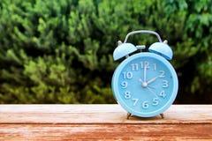 秋天时间变动的图象 后退概念 烘干叶子和葡萄酒闹钟在木桌上 免版税库存照片