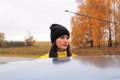 秋天时间:摆在反对一个秋季桦树森林的一件黄色外套的美丽的女孩 免版税图库摄影