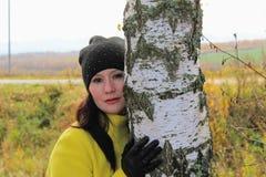 秋天时间:摆在反对一个秋季桦树森林的一件黄色外套的美丽的女孩 免版税库存图片