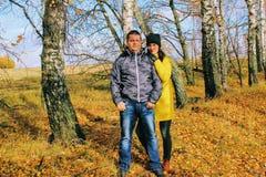 秋天时间:摆在反对秋天桦树森林背景的年轻夫妇  免版税库存图片