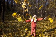 秋天有乐趣的女孩公园 免版税库存照片