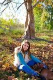 秋天有爱犬的孩子女孩在秋天森林里放松了 免版税库存图片