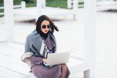 秋天来 一个美丽的年轻俏丽的女孩在大阳台上花费她的时间,当研究膝上型计算机时 库存图片