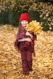 秋天林分的一个女孩与束黄色叶子 库存照片