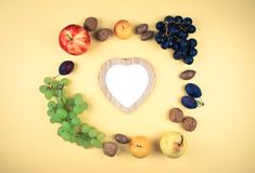 秋天果子和坚果在黄色背景 免版税库存图片