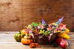 秋天柳条筐与蓝色花的桌焦点 免版税图库摄影