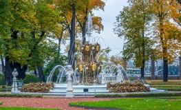秋天树、古老大理石象、草坪和小瀑布f看法  免版税图库摄影