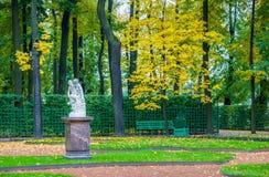 秋天树、古老大理石象、草坪和benche看法  免版税库存照片
