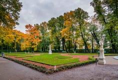 秋天树、古老大理石象和草坪看法在夏天 免版税库存照片