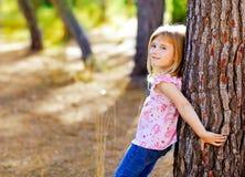 秋天树干的白肤金发的孩子女孩 图库摄影