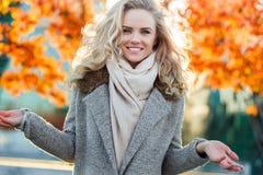秋天树背景的美丽的微笑的逗人喜爱的白肤金发的女孩  免版税图库摄影