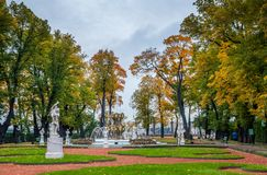 秋天树,古老大理石象,草坪,喷泉看法和 免版税库存图片