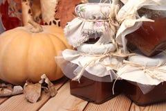 秋天桌、南瓜和果酱瓶子木表面上 库存图片