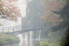 秋天桥梁有薄雾的老公园 库存照片
