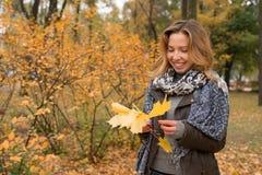 秋天森林五颜六色的叶子的愉快的女孩 免版税库存图片
