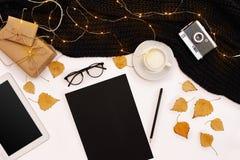 秋天概念、干秋天叶子、杯子可可粉,老照相机、围巾和片剂有黑屏的 嘲笑 免版税库存照片