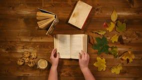 秋天概念顶视图 书,槭树叶子,烘烤老木桌 妇女纸卷通过书页 股票录像