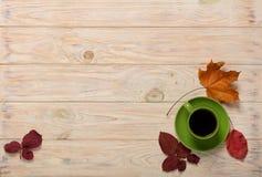 秋天概念 咖啡和秋叶在木的光 图库摄影