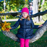 秋天概念-小女孩坐在秋天pa的树枝 免版税库存照片