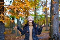 秋天概念-愉快的妇女投掷的叶子在公园 库存照片