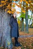 秋天概念-美丽的妇女全长画象在公园 库存照片