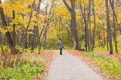 秋天概念-走本质上的美丽的年轻现代妇女 库存图片