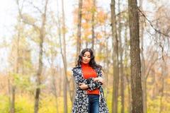 秋天概念-走本质上的美丽的年轻现代妇女 库存照片